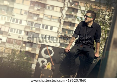 Urban portrait of one young man in skate park - stock photo