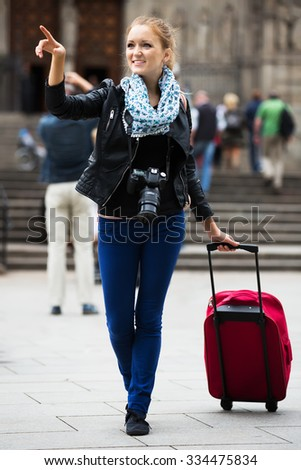 Urban portrait of young woman traveler with photo camera
