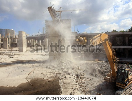 Urban renewal in the city centre. Digger working during dismantling - stock photo