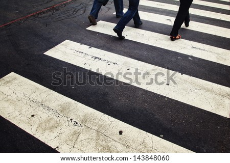 Urban road crossing with pedestrians. - stock photo