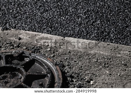 Urban road under construction, asphalting in progress. Dirty sewer manhole cover lays on a roadside - stock photo