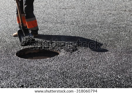 Urban road under construction, asphalting in progress, worker with a shovel near sewer manhole - stock photo