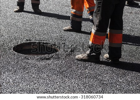 Urban road under construction, asphalting in progress, workers near sewer manhole, feet fragment - stock photo