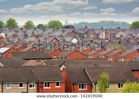 Urban scene across built up area showing the slate roof tops of terraced houses on an old housing estate - stock photo