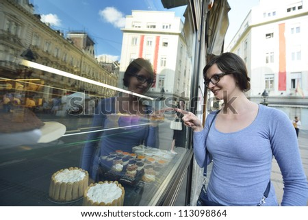 urban scene of young woman in front of sweet candy food store window - stock photo