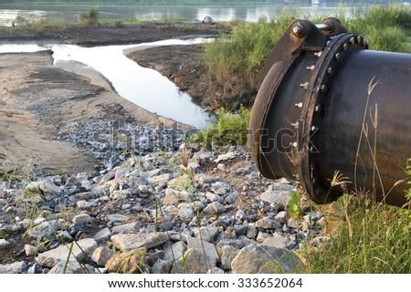 Urban sewage drain pipr ,into the river - stock photo