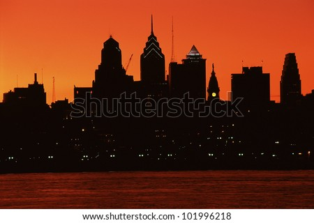 Urban skyline silhouetted by sunset - stock photo