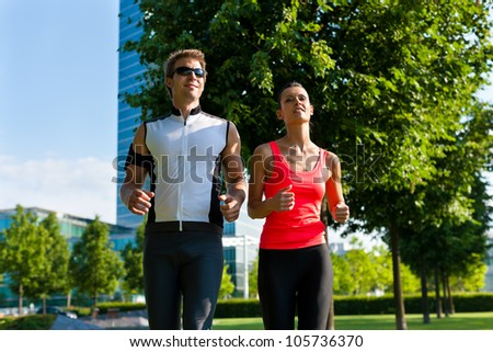 Urban sports - couple jogging for fitness in the city on a beautiful summer day - stock photo