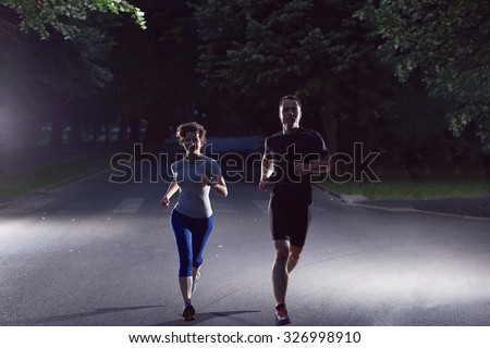 urban sports, healthy couple jogging in the city at early morning in night - stock photo
