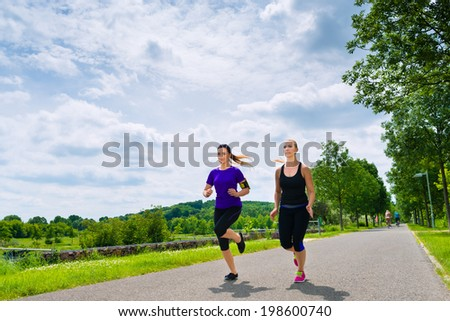 Urban sports - two women or female friends running together for better fitness in the city park on a cloudy summer day
