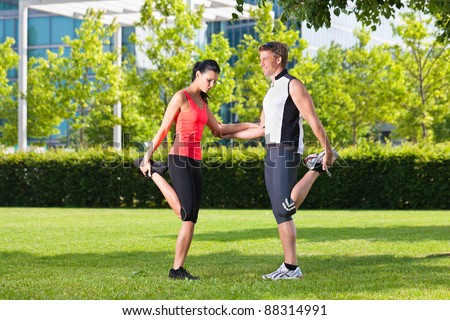 Urban sports - young couple is doing warming up before running in the city on a beautiful summer day - stock photo