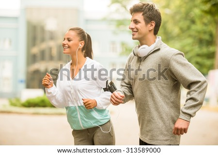 Urban sports. Young happy couple running outdoors.