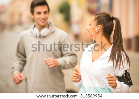 Urban sports. Young happy couple running outdoors. - stock photo
