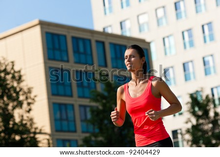 Urban sports - young woman jogging for fitness in the city on a beautiful summer day - stock photo