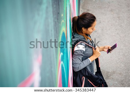 Urban sporty woman texting or messaging on smartphone after outdoor workout. Female athlete leaning on a city wall.