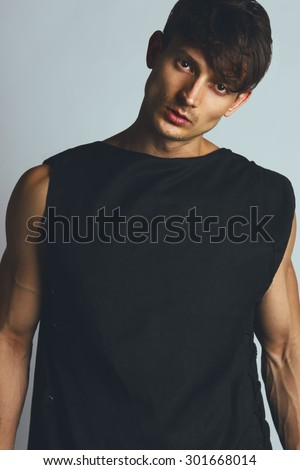 Urban street concept. Portrait of handsome male model in black clothes posing over gray background. Close up. Studio shot. - stock photo