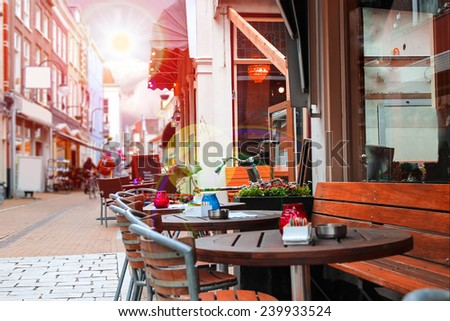 Urban street with a picturesque cafe in rays sun - stock photo
