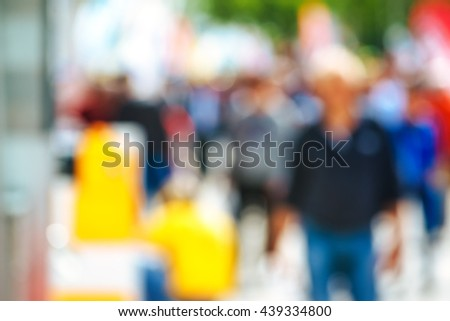 Urban street with pedestrians out of focus, unrecognizable everyday people - stock photo