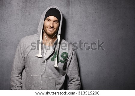 Urban style young man smiling happy, leaning against grey wall, wearing hooded jumper. - stock photo