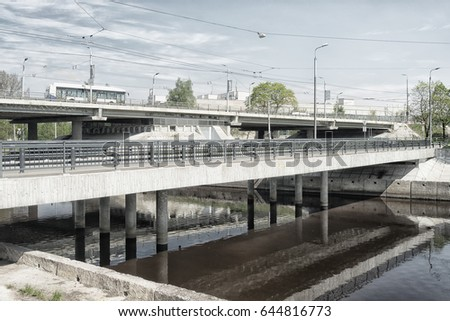 Urban summer landscape with iron-concrete bridge over the canal in Riga in the high key