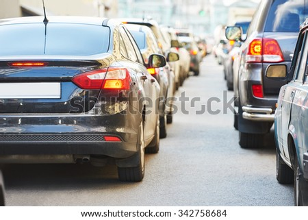 Urban traffic jam with rows of cars in a city street road during rush hour - stock photo