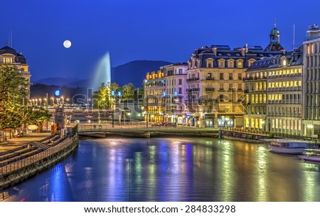 Urban view with famous fountain by night with full moon, Geneva, Switzerland, HDR - stock photo