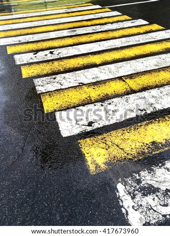 urban wet road with zebra crossing in rain - stock photo