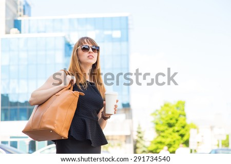 Urban woman commuter walking drinking coffee. Business woman in the city. Cheerful woman in the street drinking morning coffee. Happy young trendy woman drinking take away coffee and walking with bags - stock photo