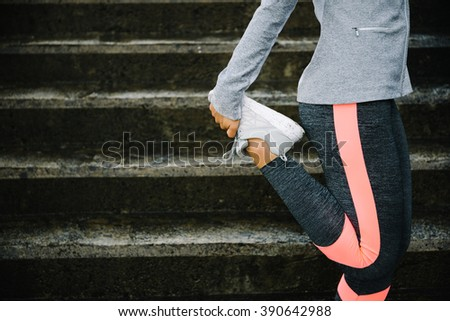 Urban workout and running concept. Woman stretching legs for warming up before exercising and climbing stairs. - stock photo
