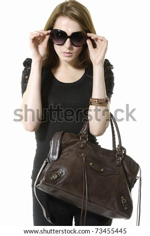 Urban young fashion model in sunglasses with modern a handbag
