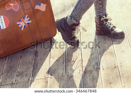 Urban young girl, standing on the street next to a suitcase - stock photo