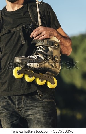 Urban young man holding his skates on the shoulder. Roller Concept - stock photo