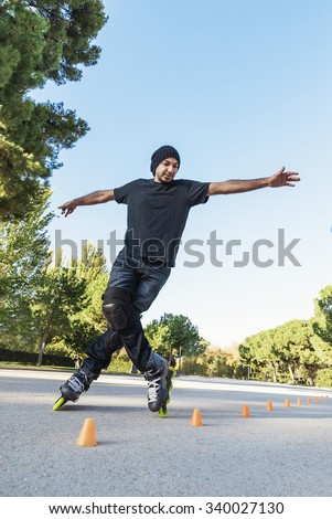 Urban young man on roller skates on the road at summer time. Roller Concept - stock photo
