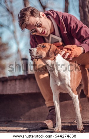 Urban young man petting a dog on autumn day