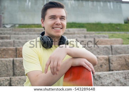 Urban young man with skateboard sitting on stair steps