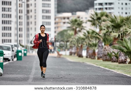 Urban young mixed race female busy running on the side walk with palm trees along side and a city scape behind her as a backdrop - stock photo