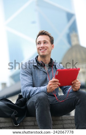 Urban young professional man using tablet computer sitting in Hong Kong outside using app on 4g wireless device wearing headphones. Casual young urban professional male in his late 20s. - stock photo