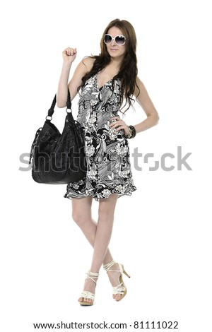 Urban young woman in sunglasses holding black handbag