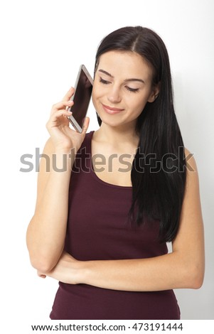 Urban young woman talking on smart phone in studio. Casual young businesswoman wearing shirt and jeans. Beautiful female model its 20s.