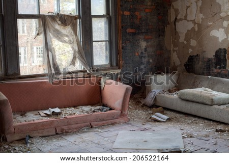 Urbex - Interior of abandoned house with broken sofas and asbestos tiles, in light HDR processing - stock photo