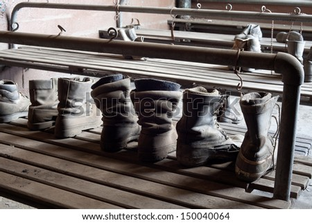 Urbex - Workers shoes left behind in abandoned factory - stock photo