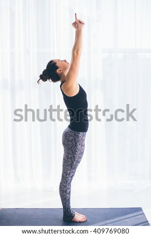 Urdhva hastasana. Beautiful yoga woman practice in a training hall background. Yoga concept. - stock photo