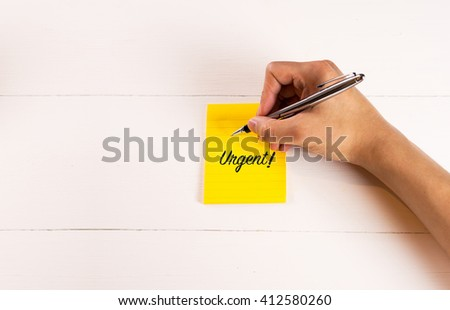 Urgent on sticky note with handing writing on wood wall - stock photo