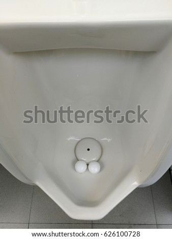 Urinal for men in toilet room with white naphthalene balls for unwanted smells