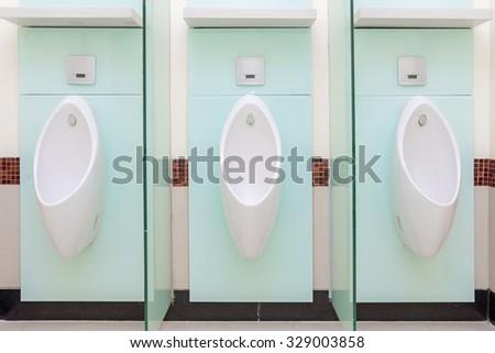Urinals Men public in toilet room, wc. - stock photo
