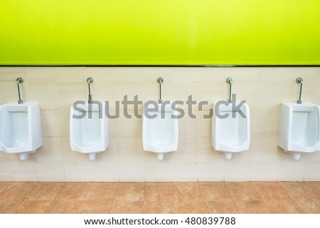 Urinals on green and tiled wall