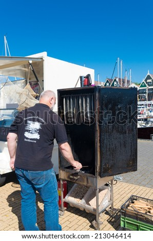 URK, NETHERLANDS - MAY 31, 2014: Unknown man keeping an eye on a smokehouse with eel during the annual fishing days. - stock photo
