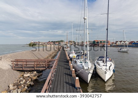 URK, THE NETHERLANDS - AUG 29: Wooden pier and moored sailing ships with tourists on August 29, 2015 in the harbor of Urk, the Netherlands
