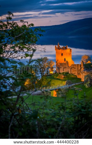 Urquhart Castle at twilight. The castle sits beside Loch Ness, near Inverness and Drumnadrochit, in the Highlands of Scotland. Only the bright part of the castle is in focus; the rest is blur. - stock photo