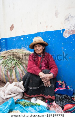 URUBAMBA, PERU - JANUARY 3: Quechua woman selling produce on market on January 3, 2010 in Urubamba, Peru. The market in Urubamba is one of the largest and liveliest in the Sacred Valley of the Incas. - stock photo